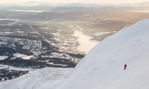 Widescreen shot of a ski slope near the Swedish town of Åre. A lone skier is pictured skiiing the slope with the town asa a backdrop behind.