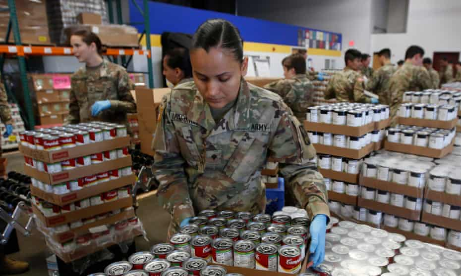 Specialist Yadira Izaguirre of the California national guard picks up case of soup that will be packed with other supplies at a food bank in Sacramento, California.