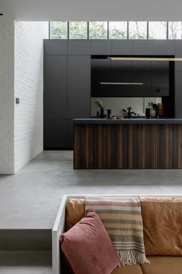 Behind the sunken living room, the kitchen rises to double-level height.