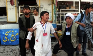An injured victim is aided after a suicide bomb attack on a protest by ethnic Hazaras, in Kabul.