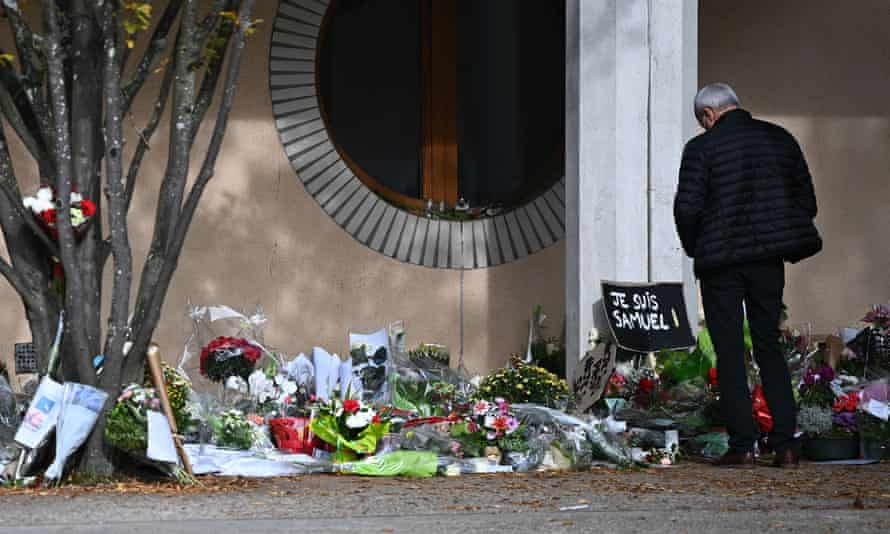 A man looks at flowers outside the Bois d'Aulne secondary school in homage to Samuel Paty.