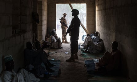 Nigerian soldiers stand guard next to civilians