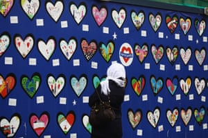 A woman looks at a memorial outside Notting Hill Methodist church