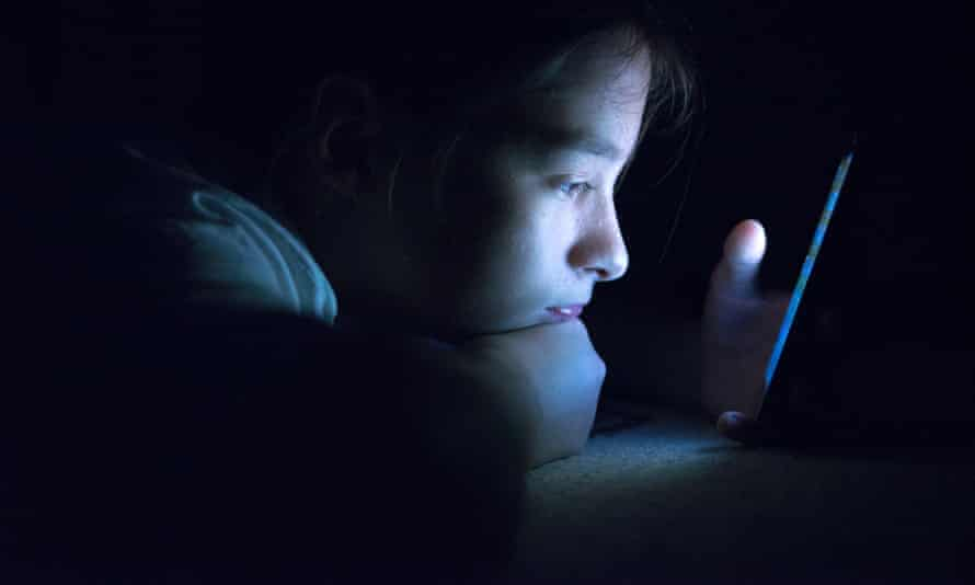 Child looking at screen in bed