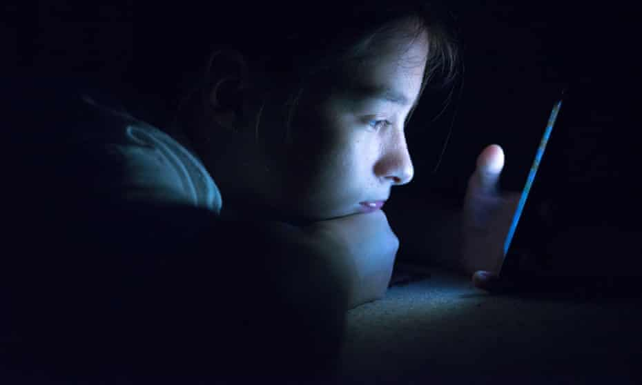 Teenager sending email from smart phone in her bed,