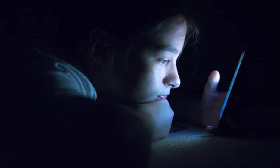 A teenager using a smartphone in bed