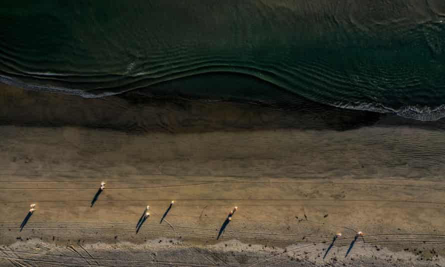 An aerial view of environmental oil spill cleanup crews picking up oil chucks off the beach from a major oil spill at Huntington Beach.