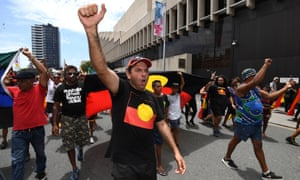 """Indigenous protesters march through central Brisbane to protest what the call """"Invasion Day"""", 26 January 2017."""