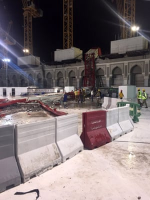 Saudi emergency teams stand next to a construction crane.