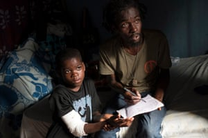 Opposition activist Jean Charles Jean Clauzel, 41, with nine-year-old Dera Lourdjy in Solino, Port-au-Prince