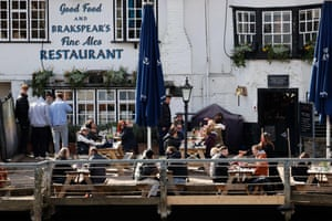 People sit in the afternoon sun in the garden of the Angel on the Bridge pub in Henley-on-Thames, London.