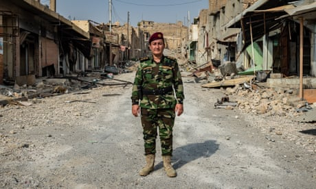 Khatoon Khider in the uniform of her Peshmerga unit stands amid the rubble of Sinjar market.