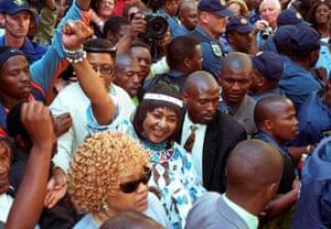 Winnie Mandela raises her fist as she leaves court in 2003