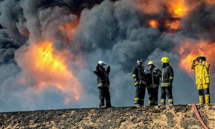 Firefighters try to extinguish an oil tank blaze after Isis militants attacked Ras Lanuf and the nearby terminal of Es Sider.