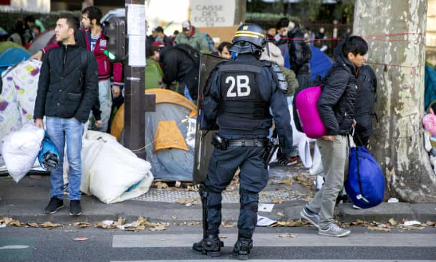 A police officer stands in front of migrants and refugees during a police operation at a shanty town in Paris.