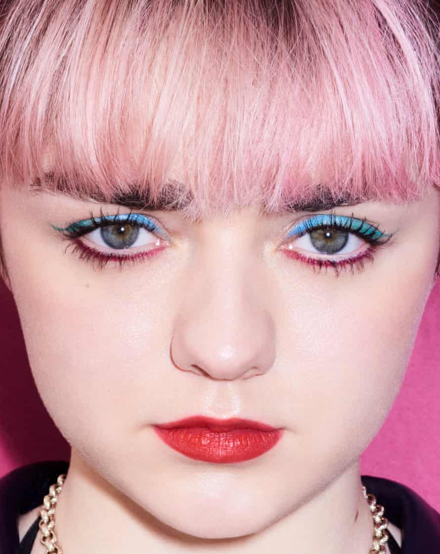 A close-up of Maisie Williams's face, with red lipstick, bright blue eyeshadow and pale pink hair