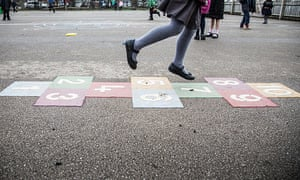 A pupil playing hopscotch in the playground of a primary school