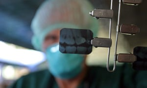 A dentist holds up x-rays