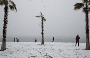 People walk on the snow-covered beach of Edem in Paleo Faliro.