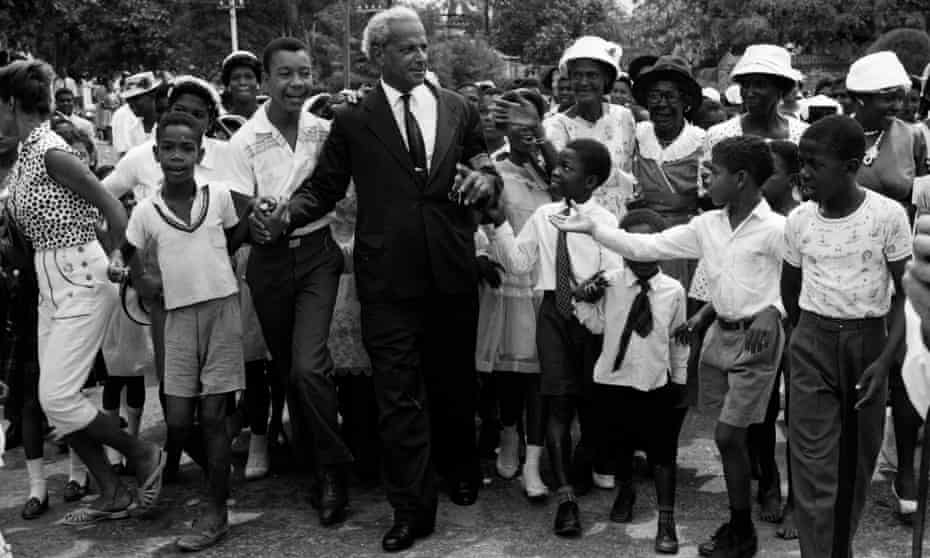 Children gather round Norman W Manley, founder of the Jamaican People's National Party, as he makes his way to the cathedral for Jamaica's Independence Day celebrations, 6 August 1962.