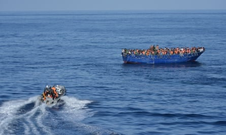 A patrol boat heads towards a boat overcrowded with migrants.