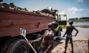 Sand diggers loading trucks at a quarry on the banks of the Congo river.