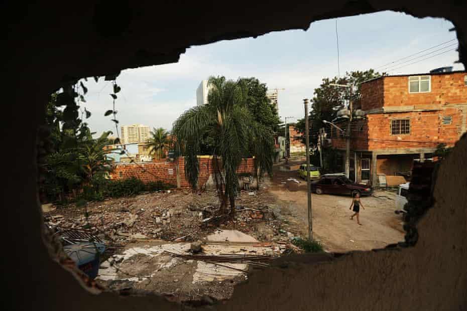A woman walks in the mostly demolished Vila Autodromo favela community