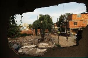 A young resident walks in the mostly demolished Vila Autódromo favela community in Rio de Janeiro, Brazil
