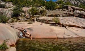 A bather dives into a natural pool of water at Charca Verde in Manzanares el Real, Madrid.