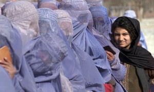 A girl waits to receive food aid among burka-wearing Afghan women during the UN food distribution scheme in Kabul, 13 December 2001.