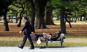 A 'salaryman' passes a homeless man in a Tokyo park.