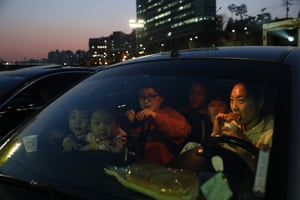 A family watches a movie from their car at a drive-in theatre in the Seongdong district of Seoul