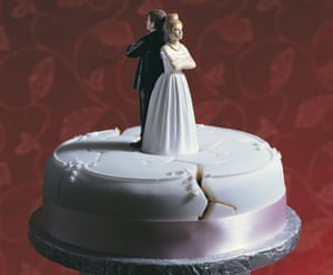 A damaged wedding cake, with bride and groom figures standing back to back