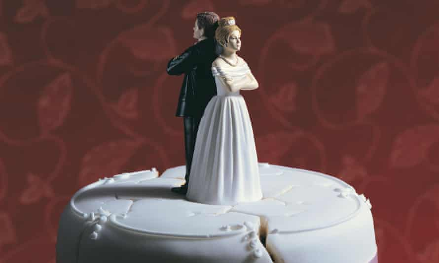 A bride and groom standing back to back on a wedding cake.