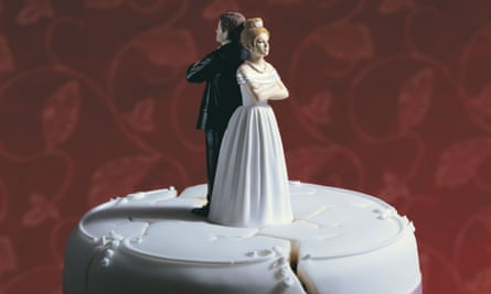 A wedding cake with a bride and groom standing back to back.