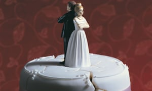 Bride and groom on broken wedding cake standing back to back