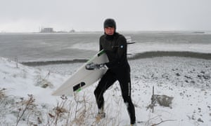 Oli Adams returns to his car after a spot of surfing in Redcar.