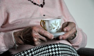 Elderly woman holding a cup of tea.