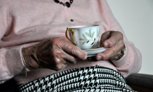 Elderly woman holding cup of tea