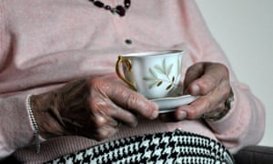 Elderly woman holds cup of tea