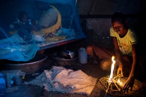 A girl builds a fire to make tea while her mother cares for a baby under a mosquito net in their shelter in Malakal camp
