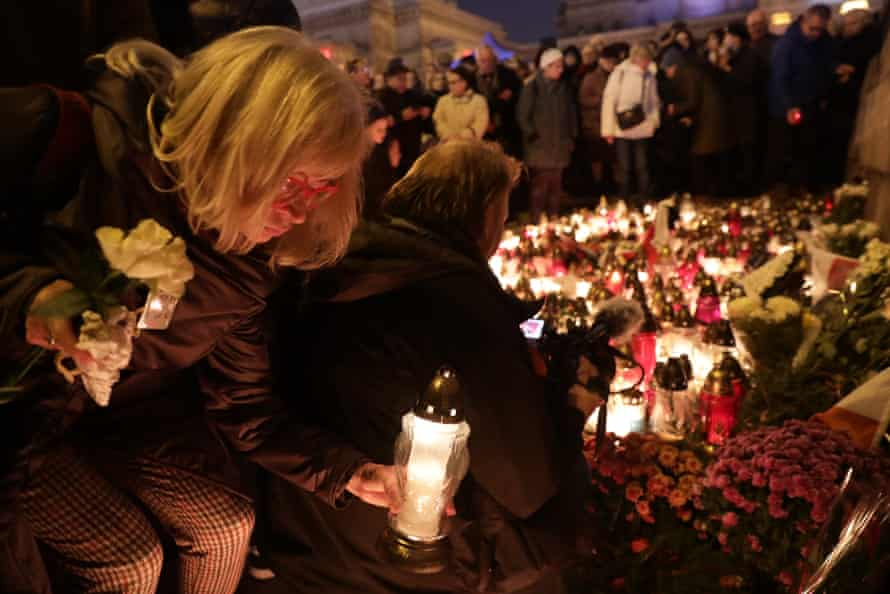 A woman lights a candle outside Warsaw's Palace of Science and Culture to commemorate Piotr Szczesny.