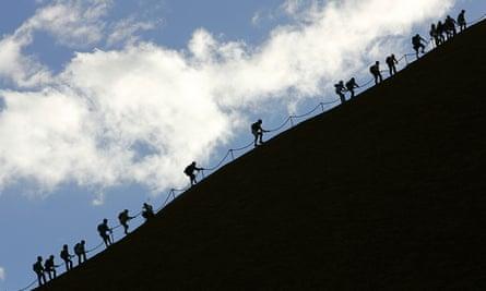 Tourists climb the monolith of Uluru