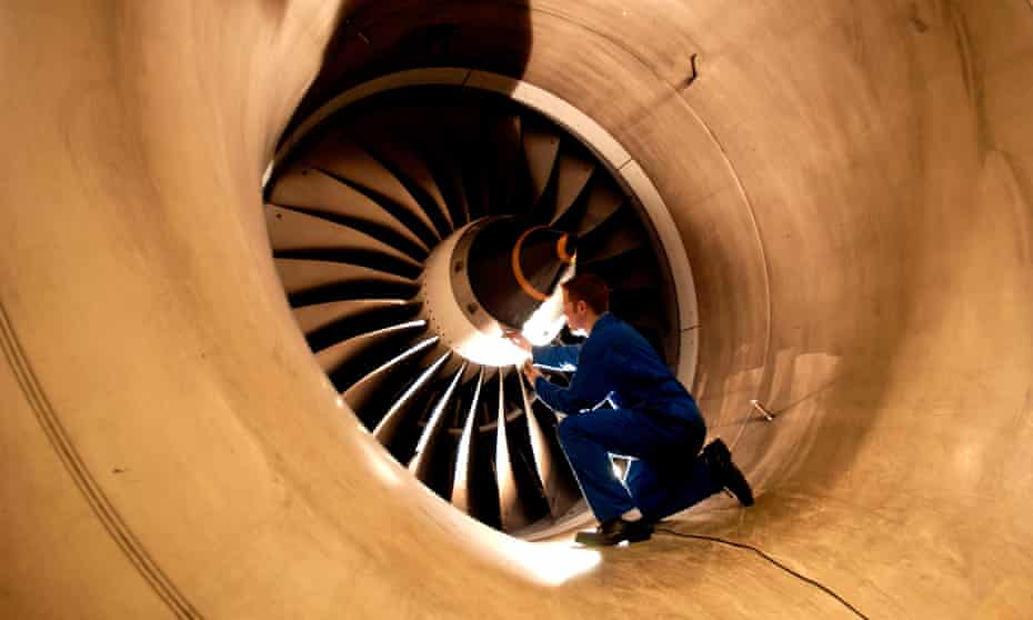 A fitter inspects the fan blades of an aircraft engine at a Rolls-Royce factory.