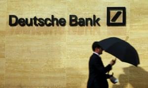 Man walking past Deutsche Bank offices in London
