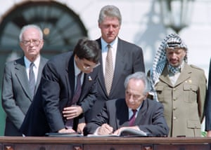 Peres signs the Oslo accords in a ceremony at the White House in Washington, watched by Yitzhak Rabin, Bill Clinton and Yasser Arafat