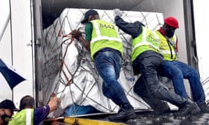 Workers load South Africa's first Covid-19 vaccine doses as they arrive at OR Tambo airport in Johannesburg.