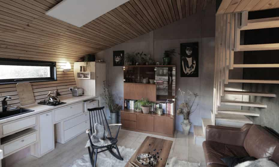 Red Kite Cabin's living room, with dining area, sofa, kitchen and small staircase.