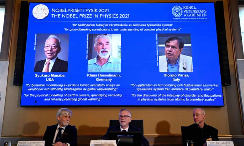 Members of the Nobel committee for physics   sit in front of a screen displaying the co-winners of the 2021 Nobel  prize, (left to right) Syukuro Manabe, Klaus Hasselmann and Giorgio Parisi, at the Royal Swedish Academy of Sciences in Stockholm