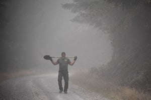 A local resident helping to put out hotspots and cut fire roads walks down a smoky road with a shovel over his shoulders, in Molalla